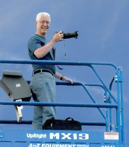 Close up of Laird with camera on top of scissors lift