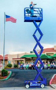 Laird 20' up on scissors lift overlooking senior living community
