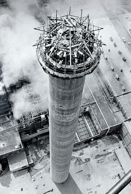 Helicopter view of tall factory smokestack