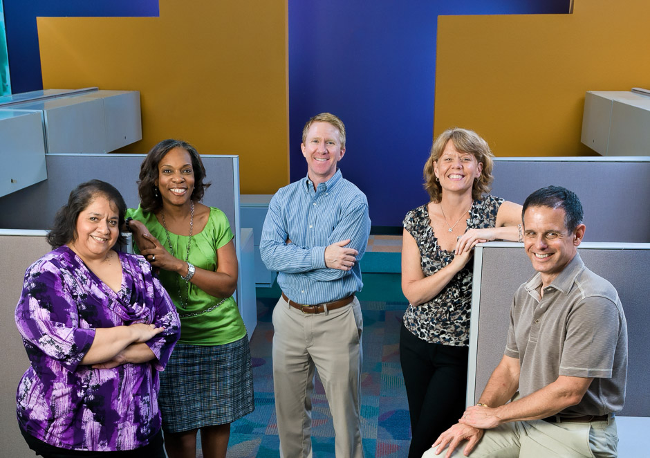 Five people in unused business cubicles posing