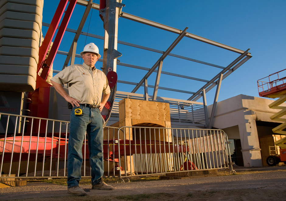 Foreman with hard hat standing in front of construction at sunrise