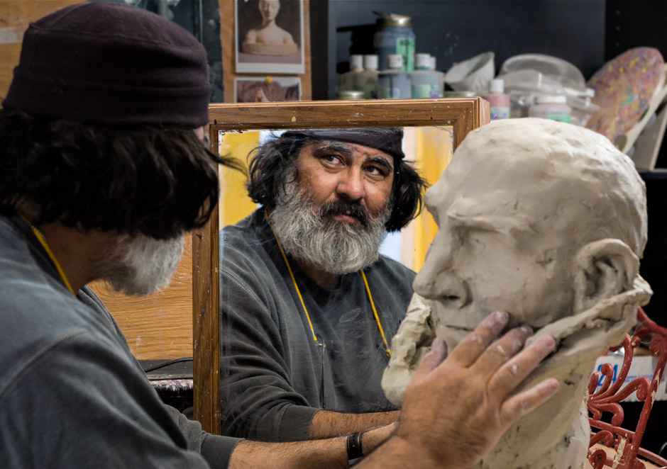 Man looking in mirror while making a bust out of clay