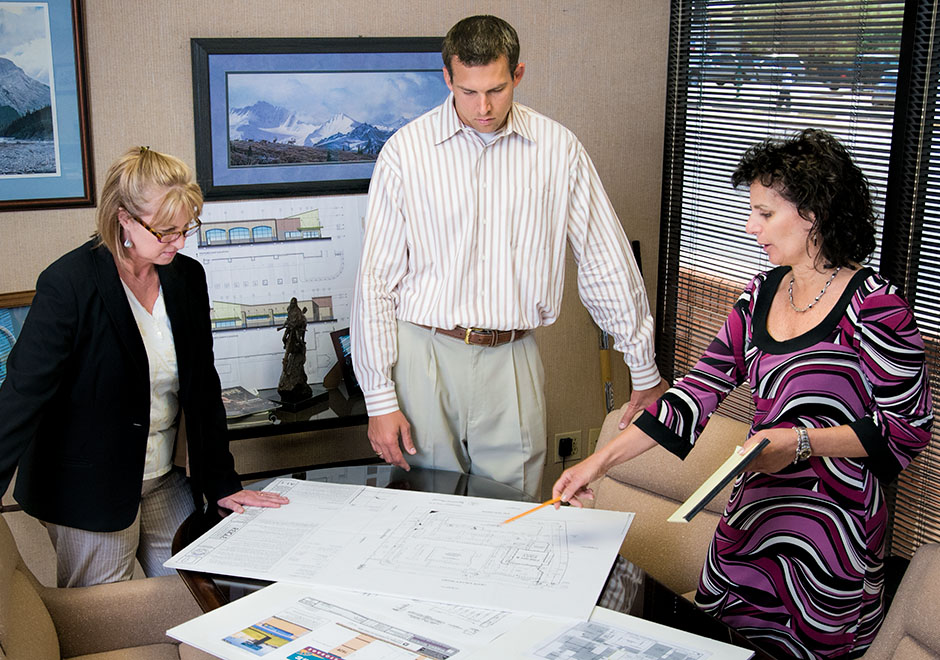 Two women and a man in executive office look at blueprints
