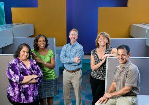 Five people in unused business cubicles talking