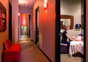 View down softly lit hallway and, looking through door, see massage technician working on person.