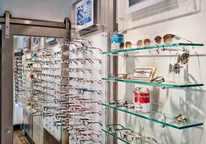 Wall of eye glasses display with sliding door in background