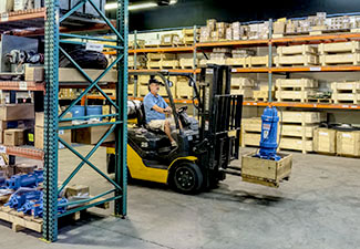 Warehouse with man driving a fork lift with large pump.