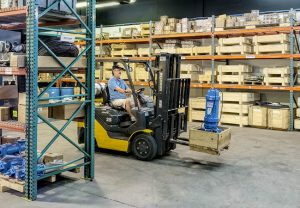 Man driving fork lift in warehouse