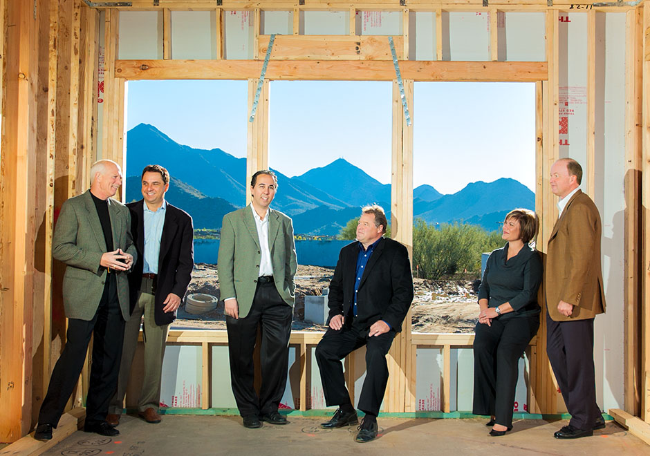 Six executives standing in window of framed-in house with mountains in background.